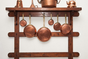 Copper pots and pans hanging from a wall rack.