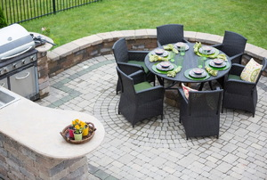 Brick patio with grill and black table with chairs