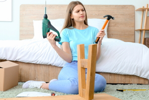 woman with drill and hammer working on table and looking confused
