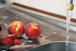 A kitchen sink with peaches and running water.