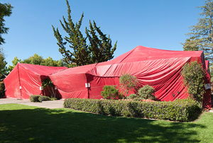 A home covered in a red termite fumigation tent.