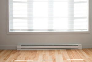A white baseboard heater in a room with a hardwood floor.