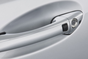 A close shot of the door handle and lock of a silver Mercedes.