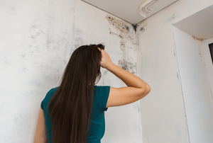 A woman looks at mold.