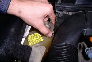 a hand holding a Radiator Cap