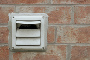 dryer vent outside mounted to a brick wall