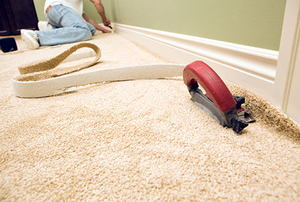 A worker cuts and installs bedroom carpet.