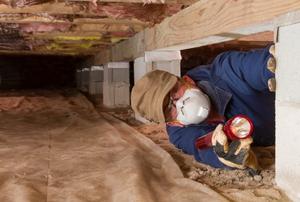 A man looks in a crawlspace.