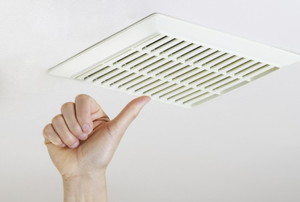 hand near a ceiling exhaust fan
