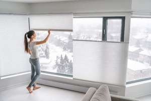 Women adjusting blinds on large window