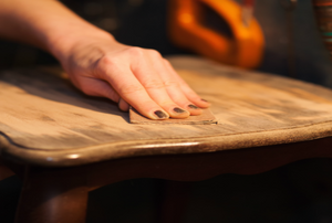 A woman works on laminate wood furniture.
