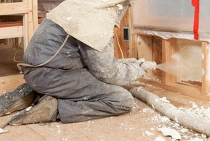 A man works on spray foam insulation.