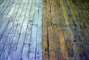 Two different colors of floorboards making up the same floor.