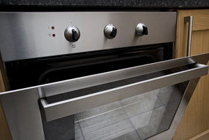 A built-in stove with the door ajar.