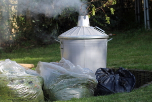 Smoke rises from a garden incinerator with lawn debris surrounding it.