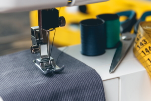 sewing machine stitching grey fabric