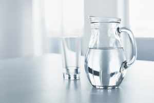 A full water pitcher and glass sitting on a gray counter in a well-lit kitchen.