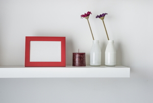 floating shelf displaying candles, flowers, and a frame