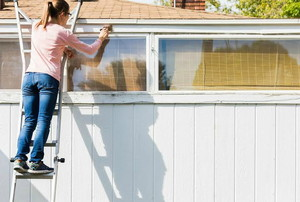 A woman standing on a ladder painting garage door trim.