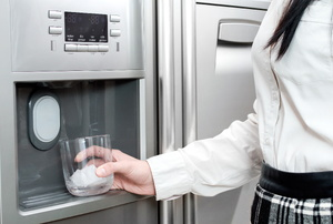 A woman getting ice in a glass from a refrigerator.