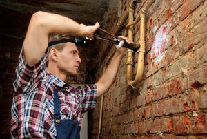 A plumber working on pipes against a brick wall.