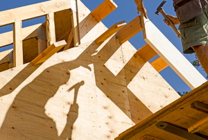 A DIYer framing a house with his shadow cast on the plywood.