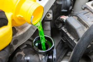 pouring green coolant into a car radiator