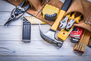 A tool belt with a variety of tools spilling out.