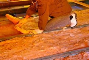 A man installing glass-wool insulation in between joists in an unfinished room.