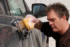 a person rubbing a sponge on a car door