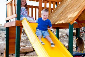 young boy on slide at playground