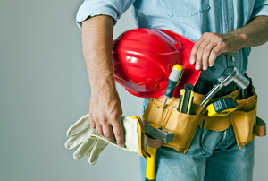 A contractor holding a hard hat and gloves.