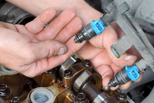 hand holding a fuel injector in an engine