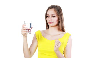 A woman in a yellow top holding a glass cup of water, looking at it questionably.