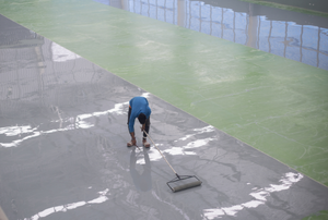 man applying epoxy to a large floor