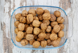 A glass tray of walnuts on a rustic wood background.