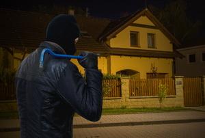 A burglar looks at a house.