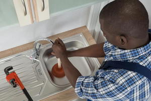 A professional plumber working with a clogged sink.