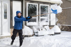 A man shoveling snow outside a house.