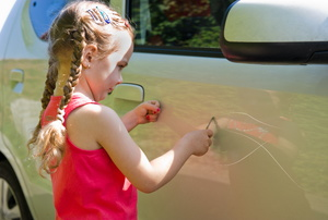 A little girl scratches a car.