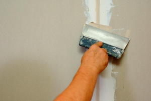 A hand applying drywall.