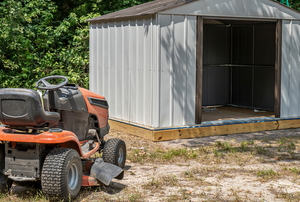 riding lawn mower near open storage shed