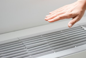 a hand above an air conditioning vent