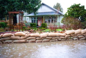 A safe home with sandbags and water surrounding it.