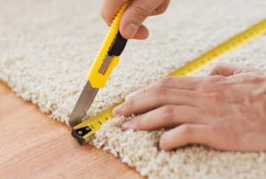 hands measuring and cutting a carpet with a tape measure and construction knife