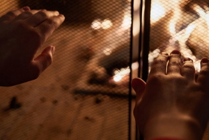 hands warming in front of fireplace grate
