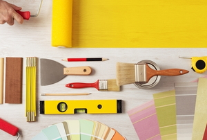 painting supplies and a hand spreading yellow paint with a roller