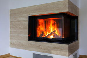An ultra-modern fireplace with a fire going.