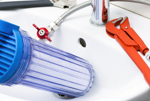 water filter with plumbing tools in sink