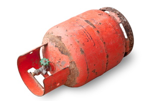 A rusty red propane take laying against a white background.
